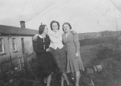 Three women in 1940s fashion in the garden of a house