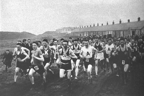 large group of runners in a competition through the mining village of Benquhat. The houses are in the background