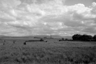 farmland with a building in the distance with a chimney stack