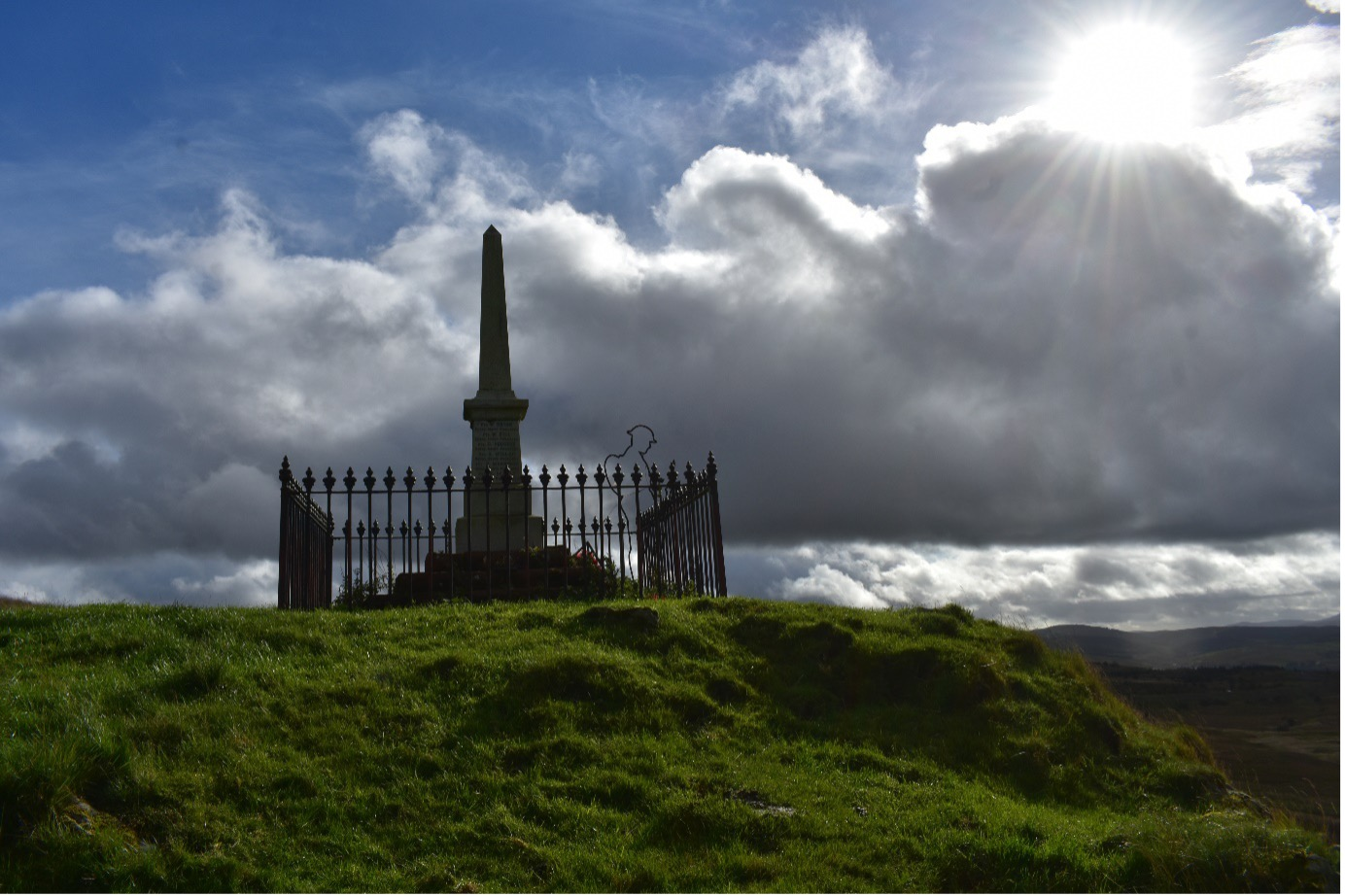 An obelisk shaped war memorial at Benwhat village Ayrshire.  On a grass hill, with railing around the monument, silhouette of a Tommy solder next to he momument with a cloudy, blue sky and son in the top left hand corner