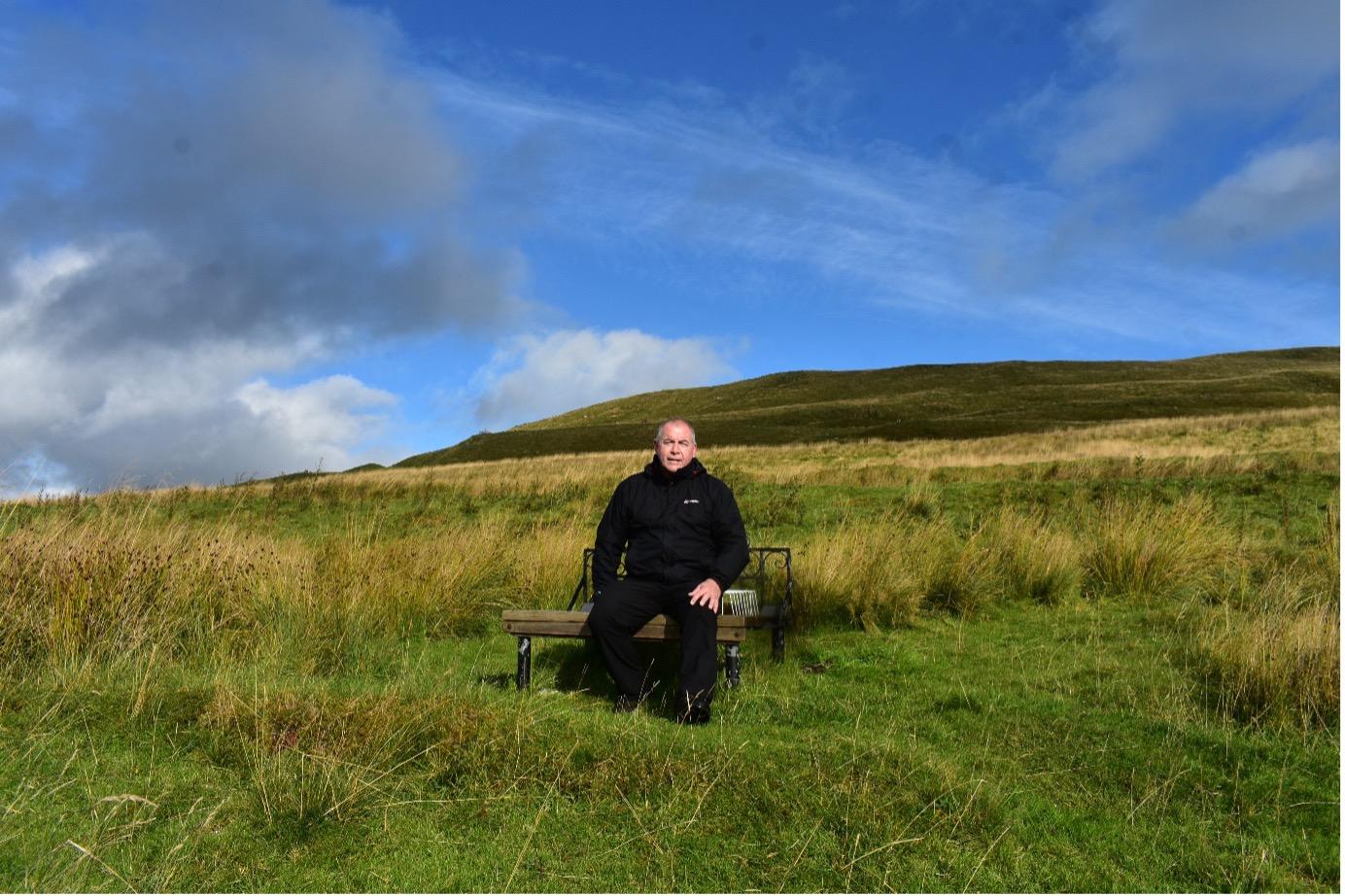 Man sitting on a bench on a hillside